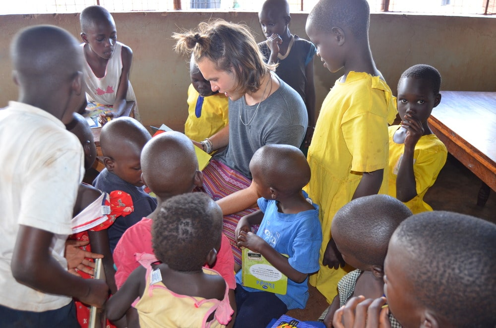 Dylan Draper, 2014 Niteo Team Member, reads to children in Jinja